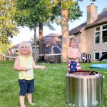 Two little boys standing by a bonfire roasting marshmallows