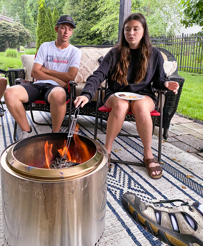 A guy and a girl sitting by the Solo Stove Bonfire Pit roasting marshmallows
