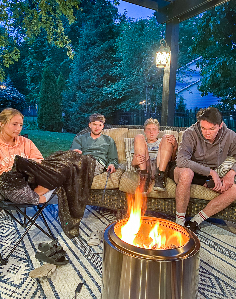 Family gathered around Solo Stove Bonfire pit mesmerized by the fire