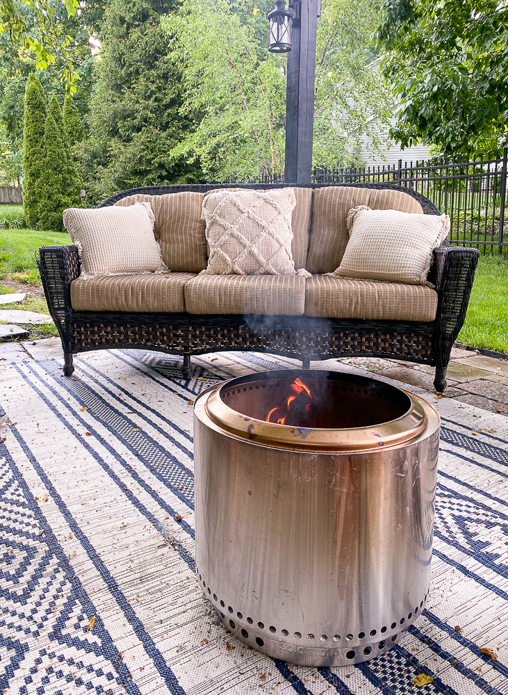 Solo Stove Bonfire Pit with smoke going straight up and an outdoor sofa in the background with 3 pillows on it