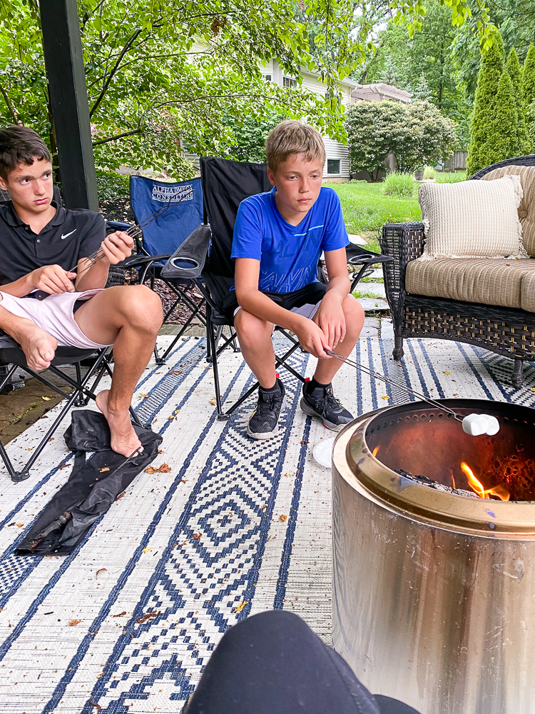 Two boys sitting by the bonfire roasting marshmallows