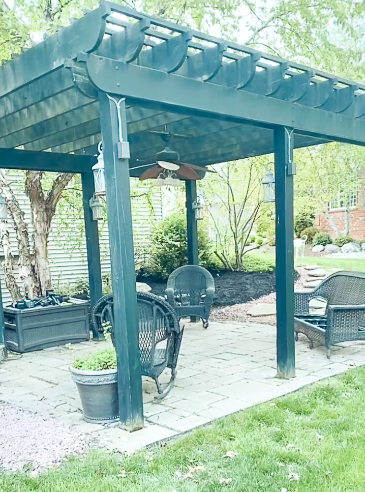 Pergola space with a couple rattan chairs and couch along with a planter