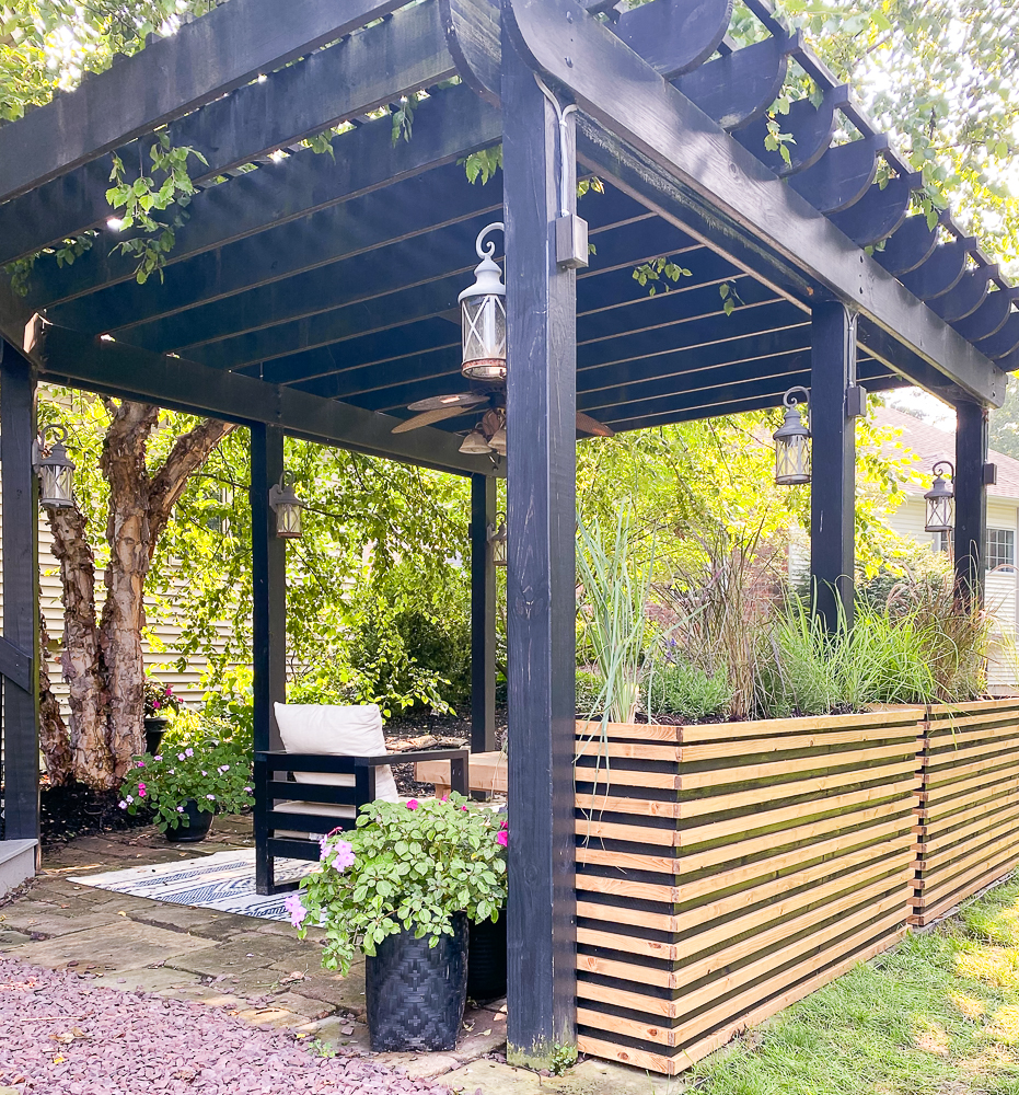 Backyard patio under a pergola with outdoor furniture and planters