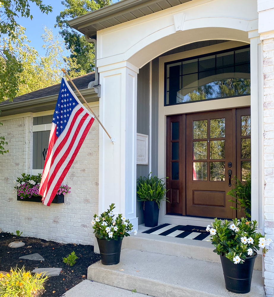 Front door of a house with an American Flag, white flowers in black vases and a faux window with a flower box