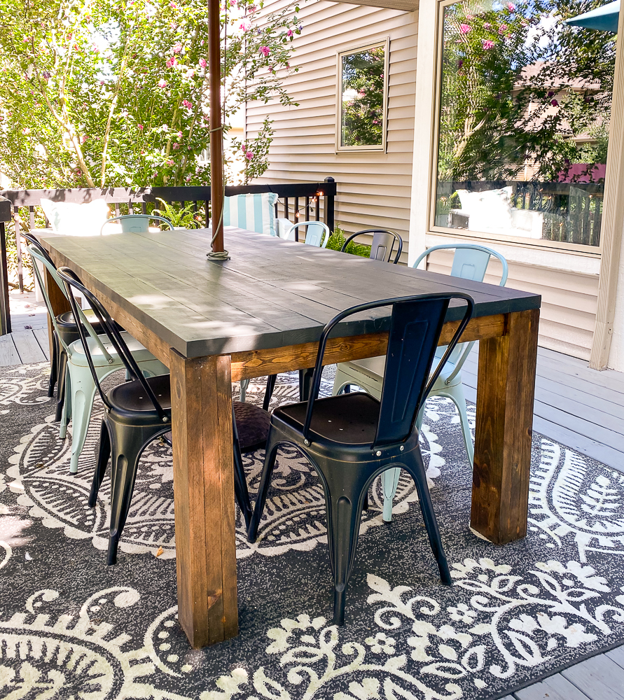 Table and chairs outside on deck with rug