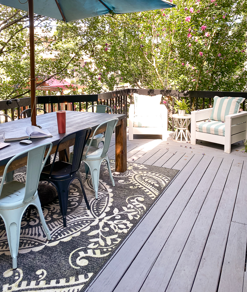 Outdoor space with a rug, table and chairs