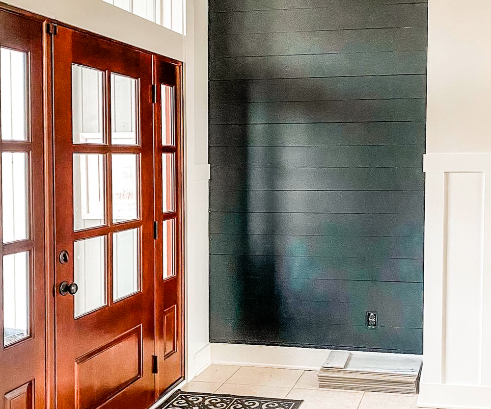 Foyer with alcove; black wall and front door with lots of windows