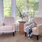 Two white chairs in a family room with a fluted side table in the middle of them